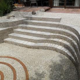 Die GartenManufactur Ragusa in Ingolstadt lässt mit Muschelkalk und einer Cortenstahl-Spirale im Zentrum des Senkgartens den ehemaligen Wildgarten in neuem Glanz erstrahlen