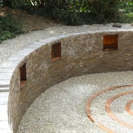 Halfpipe-Mauernischen aus Cortenstahl der GartenManufactur in Ingolstadt gliedern die Wandfläche und bieten die Möglichkeit zum Einstellen von Kerzen und Accessoires