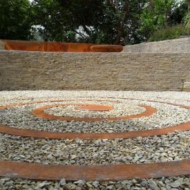 Die Spirale, die den Mittelpunkt des Senkgartens mit Sitzmöglichkeit bildet, besteht aus Cortenstahl, wirkt modern und wurde von der GartenManufactur Ragusa in Ingolstadt eingesetzt