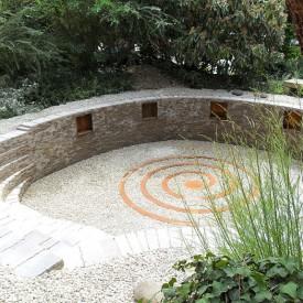 Das Herz in diesen mystischen Mauern, angelegt von der GartenManufactur Ragusa in Ingolstadt, ist die zentrierte Stahlspirale am Boden des Senkgartens, die die wilde Vegetation um den Garten herum wunderbar ergänzt