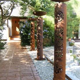 Weg zur Eingangstüre, gesäumt mit mannshohen Rohstahlsäulen mit aufgesetzten Pflanzschalen. Design der GartenManufactur Ragusa in Ingolstadt
