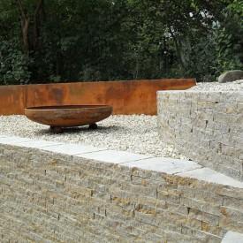 Der Senkgarten der GartenManufactur Ragusa in Ingolstadt wird komplettiert vom offenen Feuer in den Feuerschalen auf Kugelfüßen, das den Garten bei Nacht noch mystischer macht