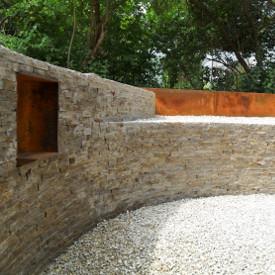Muschelkalk und das vielseitige Baumaterial Cortenstahl, das die GartenManufactur Ragusa in Ingolstadt gerne verwendet, fügen sich zu einem gemütlich, mystischen und modernen Gartenbild zusammen