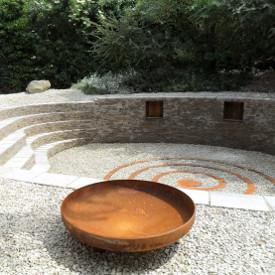 Offenes Feuer in der Feuerschale auf Kugelfüßen verstärkt den mystischen Eindruck in diesem Mystikgarten bei Dunkelheit durch Rauch, Licht und Schatten. Hergestellt von der GartenManufactur Ragusa in Ingolstadt